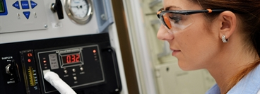 Laboratory technician wearing PPE adjusts the electrochemical analyser for trace oxygen