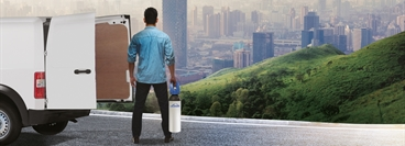 This picture, used for the MOBI campaign, shows a man standing next to a white van, holding a 10l MOBI cylinder whilst looking out over a city.