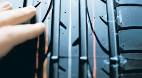 The picture shows a car tire with a prominent tyre tread. 