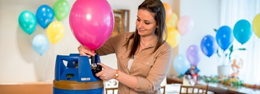 Woman using GENIE to blow up balloons. GENIE gas cylinder.