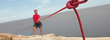 Mountain climber fixed with red safety leash.
