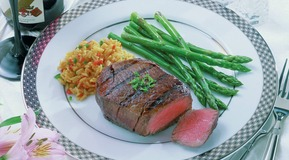 Filetsteak (medium fryed) on a plate decorated with green asparagus and rice. View on a table decoration.
